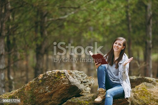 862602714istockphoto Young smiling beautiful woman sitting on stone studying reading book and spreading hands in city park or forest on green blurred background. Student learning, education. Lifestyle, leisure concept. 956317214