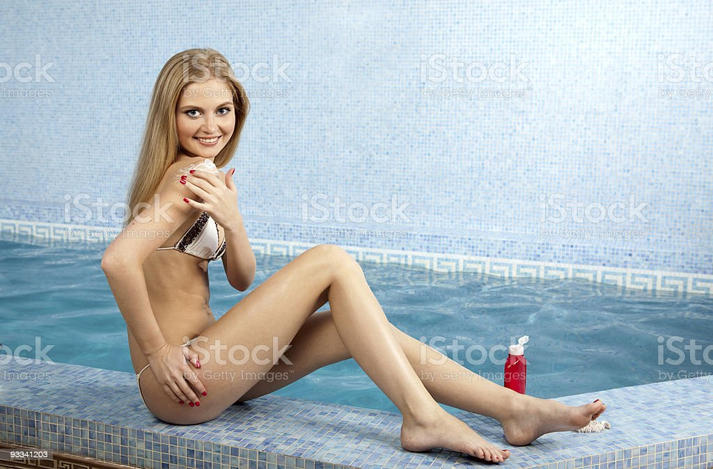 Young smiling beauty applying cream at blue pool. royalty-free stock photo