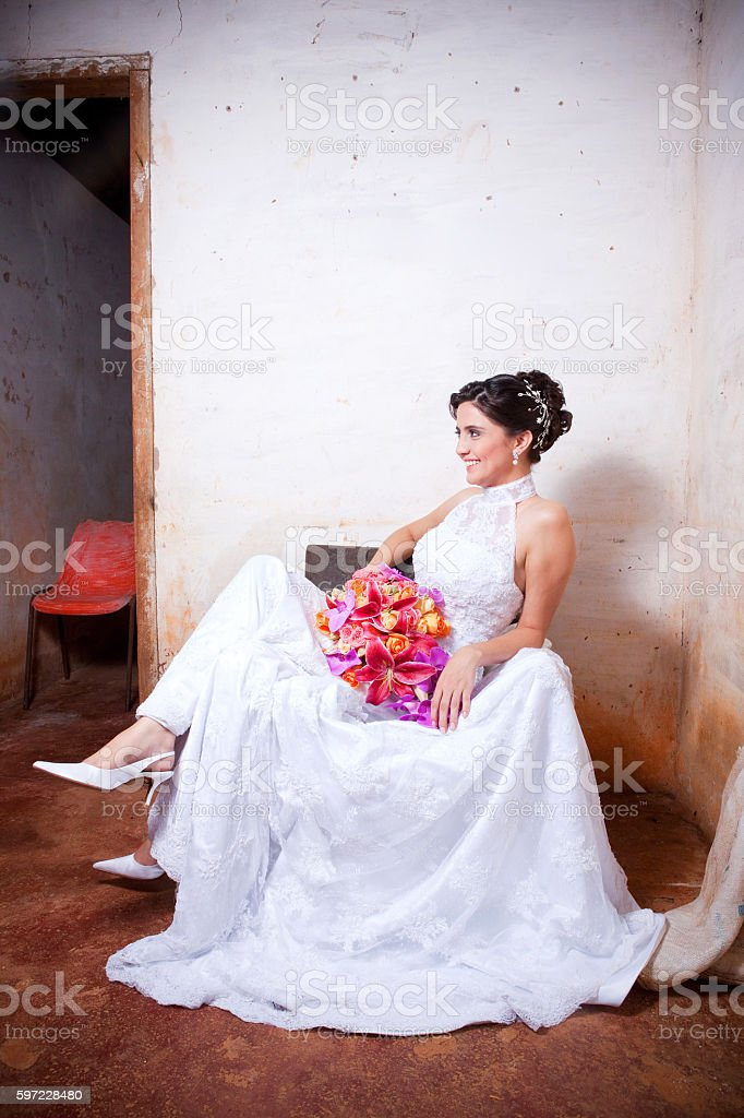 Young Smiling Bride Holding Bouquet and Sitting Inside Old Countryhouse - foto de acervo