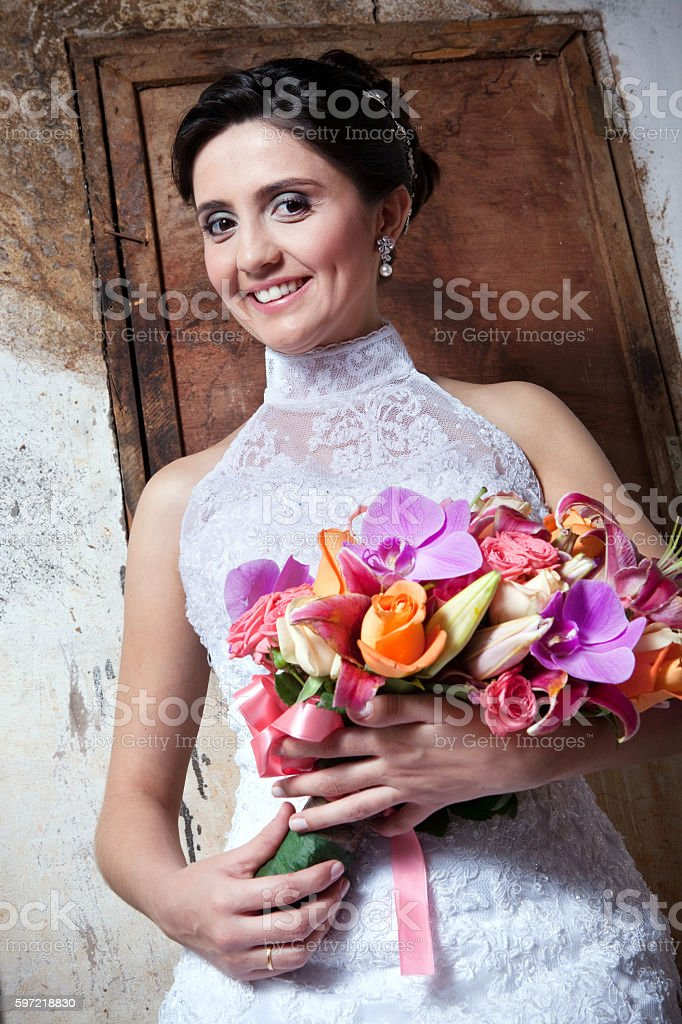 Young Smiling Bride Holding Bouquet Inside Old Countryhouse foto royalty-free