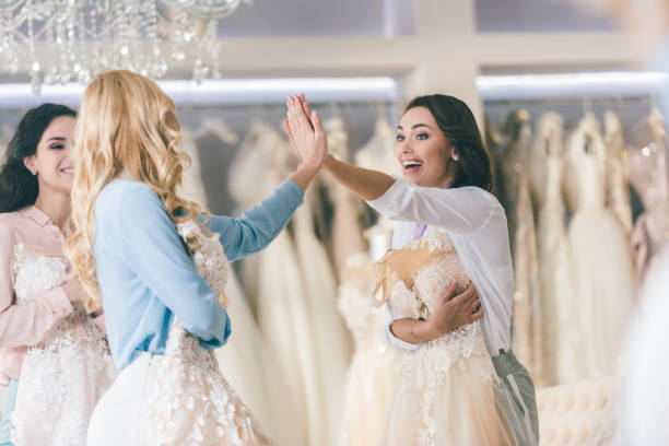 Young smiling brides giving high five in wedding atelier stock photo