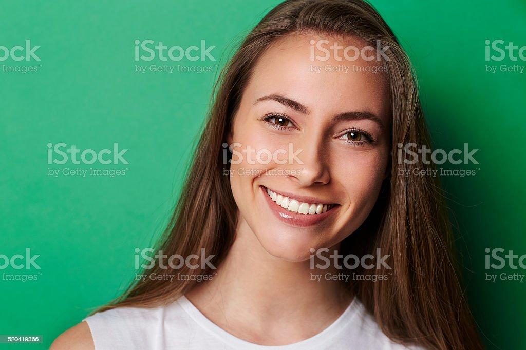 Mały uśmiech brunetka przed Zielone tło – zdjęcie