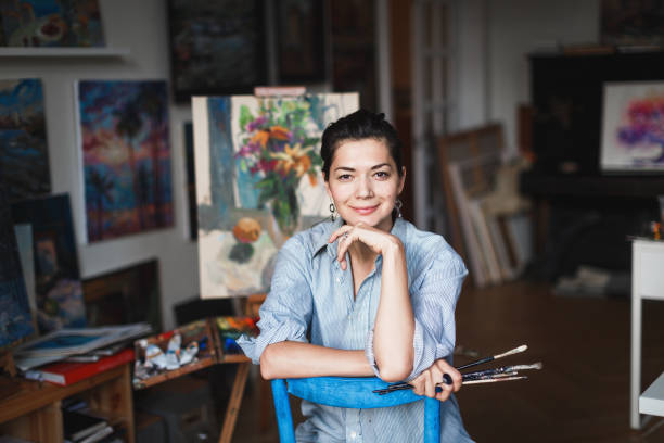 A young smiling brunette woman artist in her Studio is holding a brush. Near her easel, paintings and various art equipment. stock photo