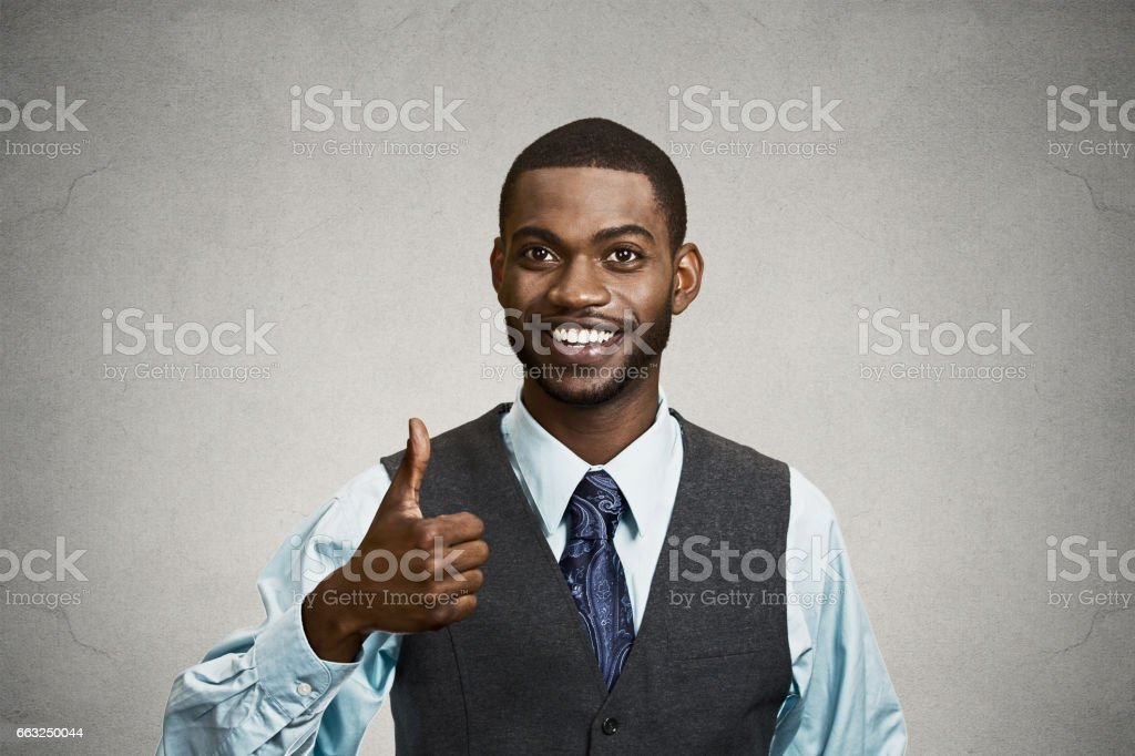 young smiling business man, corporate employee giving thumbs up sign stock photo