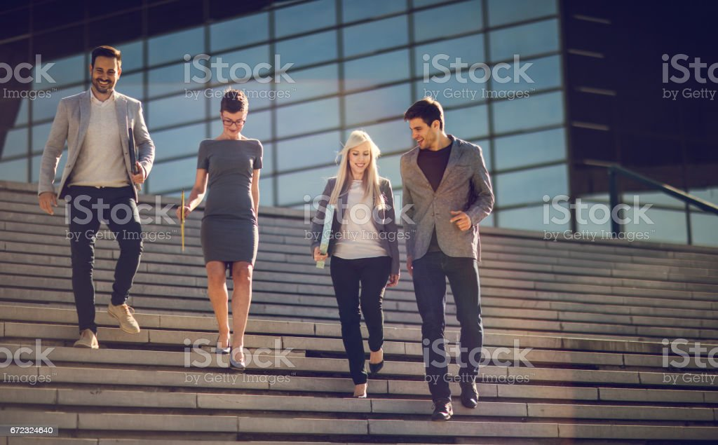 Young smiling business people walking down the stairs. stock photo