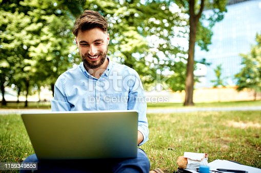 Young smiling businessman sitting on grass in park during lunch and working on laptop