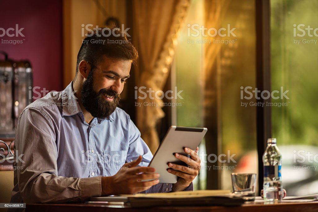 Young smiling businessman surfing the net on digital tablet. stock photo