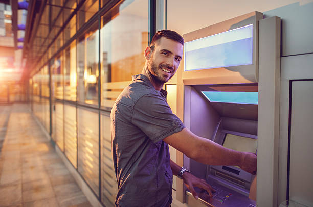 young smiling businessman withdrawing money from atm. - banks and atms stock pictures, royalty-free photos & images