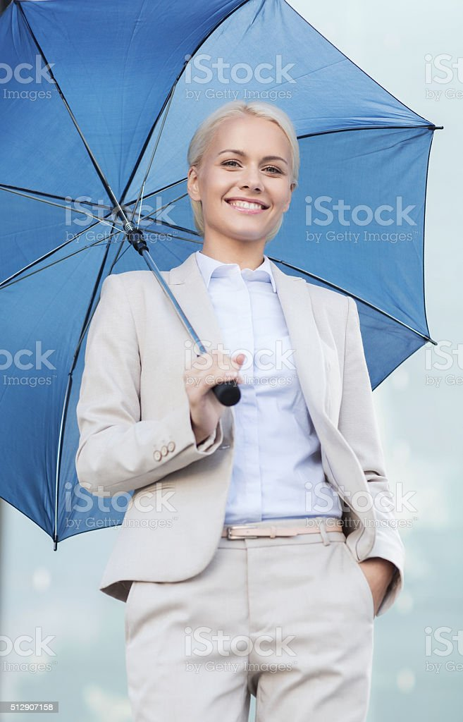 young smiling businesswoman with umbrella outdoors stock photo