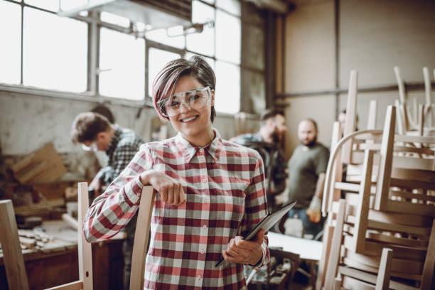 young lächelnd tischler in front of arbeiten team in ihrer werkstatt - kleinmöbel stock-fotos und bilder