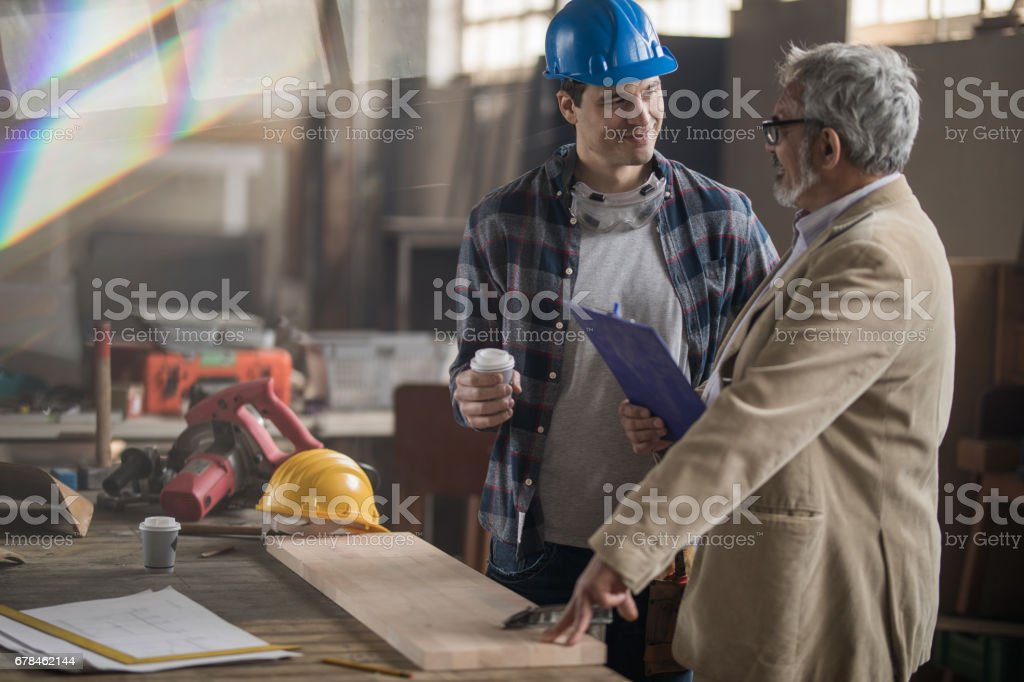 Young smiling carpenter talking to a manager in a workshop. royalty-free stock photo