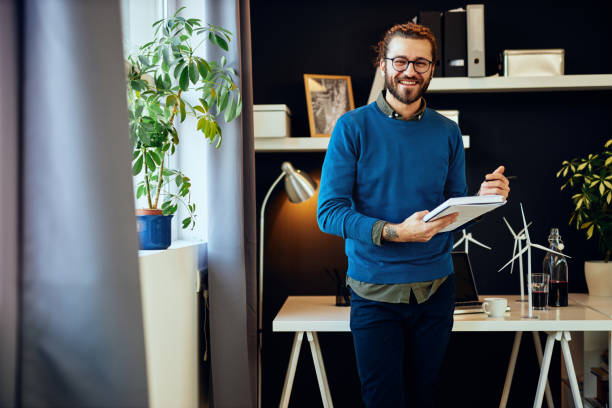 Young smiling caucasian innovative creative graphic designer standing in his office and writing ideas in notebook. stock photo