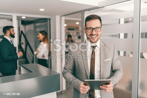 Young smiling cheerful Caucasian businessman in formal wear standing in hall and holding tablet. In background colleagues chatting. Hardest thing is to get right people.