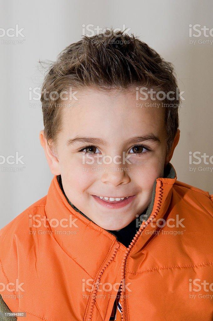 young smiling child orange jacket - series royalty-free stock photo