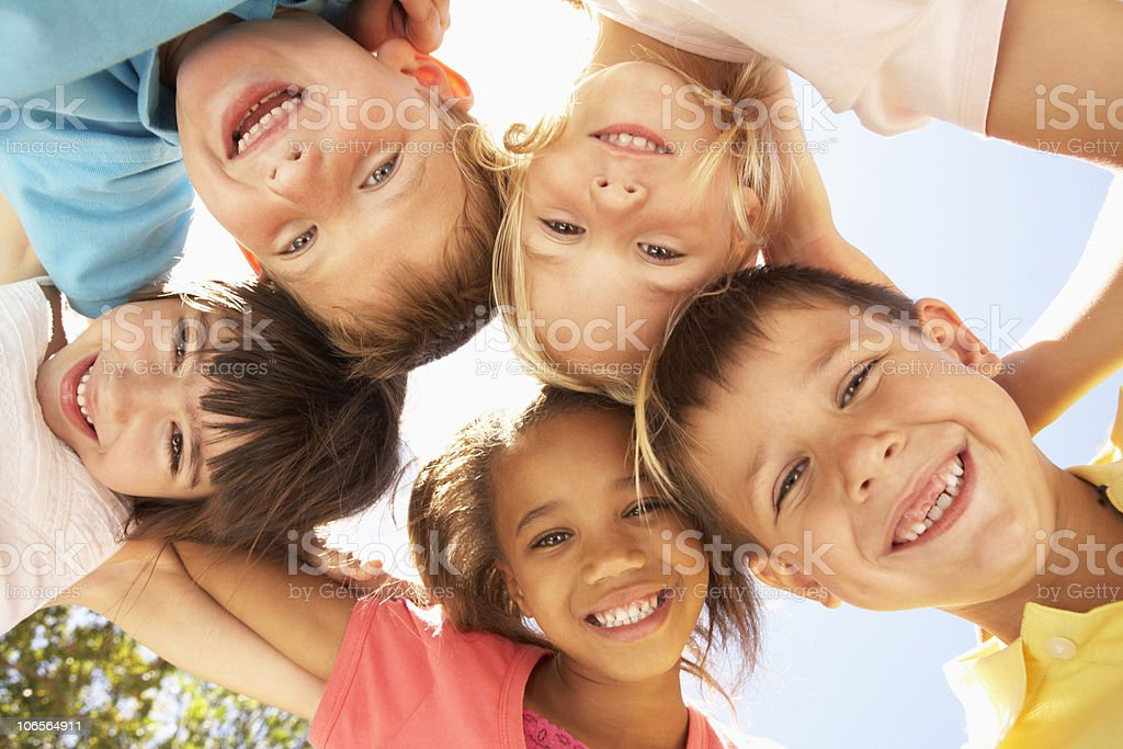 Young smiling children in a circle looking down stock photo