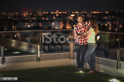 Happy couple spending night on a terrace and talking to each other.