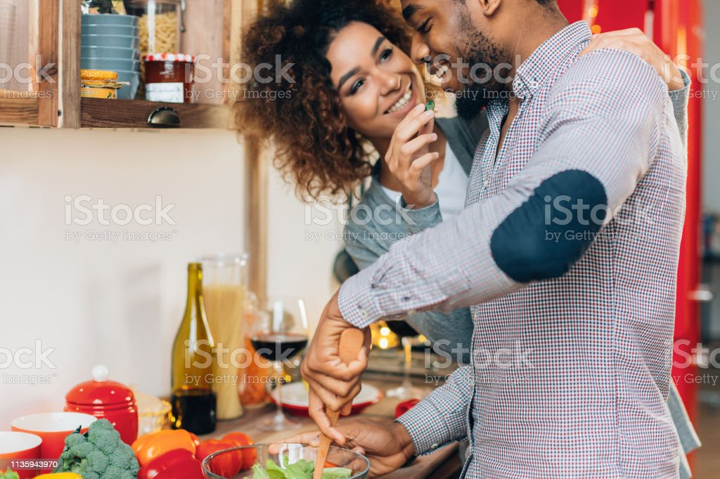 Young smiling couple eating vegetables playfully at kitchen stock photo