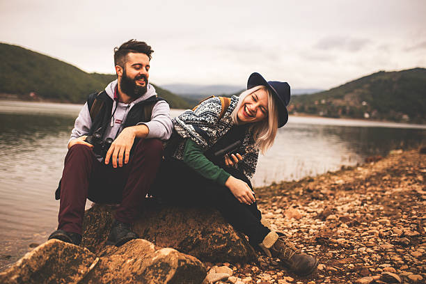 young smiling couple enjoying nature and their hiking together - calendar date stock photos and pictures