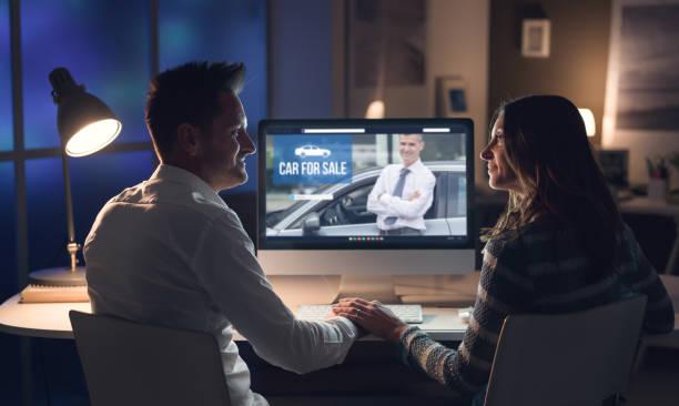 Jovem casal sorridente de mãos dadas e se conectar com um computador à noite, que estão comprando um carro online - foto de acervo