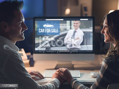 Young smiling couple holding hands and connecting with a computer late at night, they are buying a car online