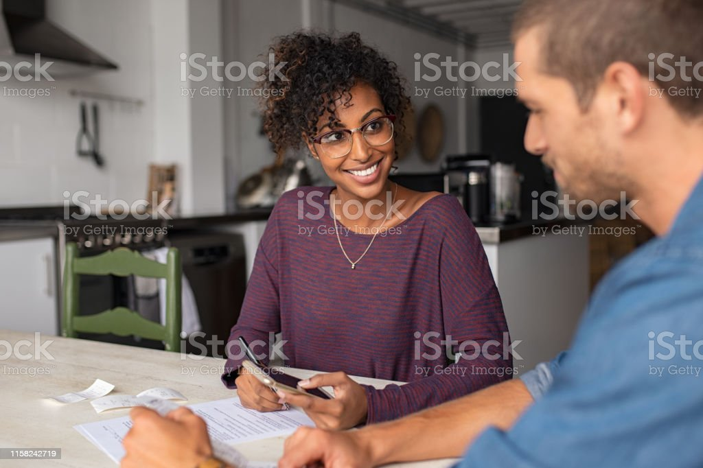 Young multiethnic couple doing accounting online with a phone bank...