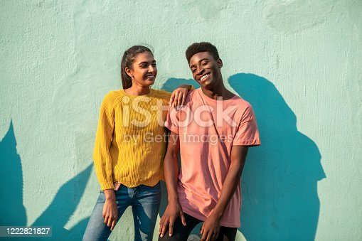 Portrait of Young happy couple. They are looking at camera while leaning on light blue wall.