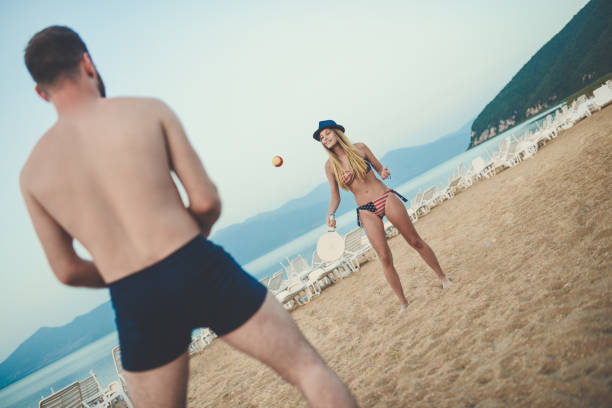 Young Smiling Couple Play Beach Tennis Paddle Ball and Having Great Time stock photo