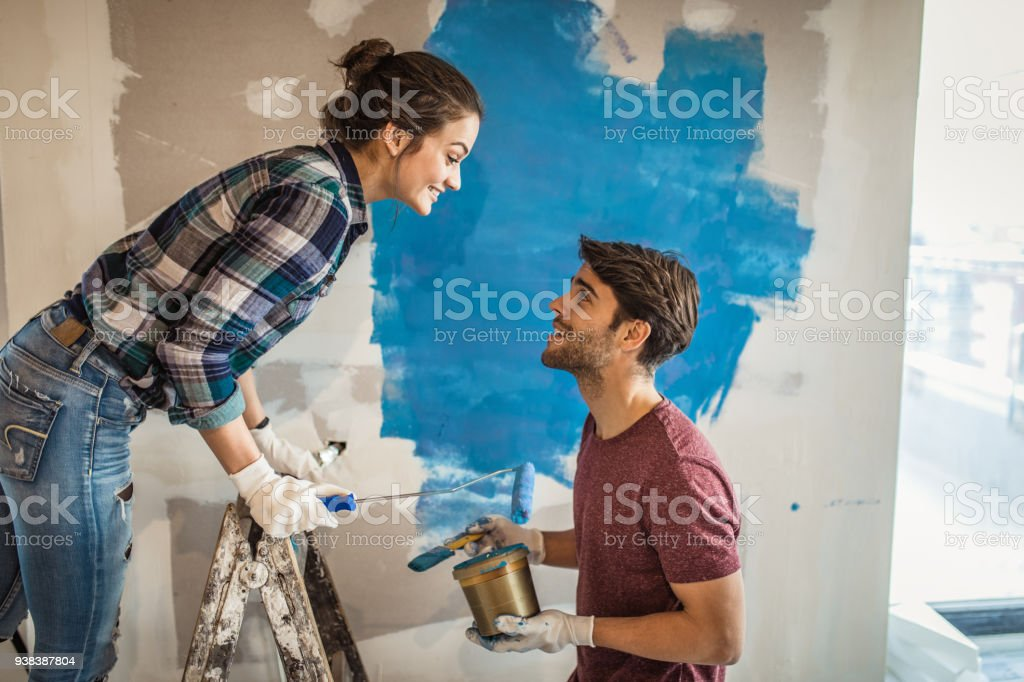 Young smiling couple talking while renovating their apartment. stock photo