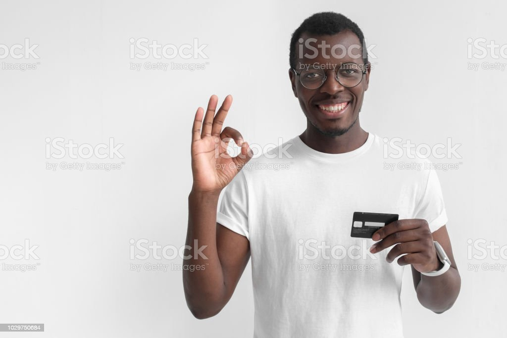 Young smiling dark skin african man in white t shirt holding credit card and showing okay sign isolated on gray background with copy space stock photo