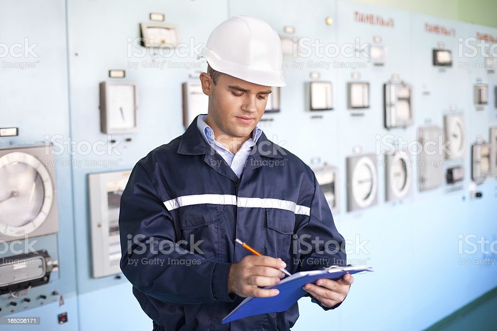 young smiling engineer taking notes in control room royalty-free stock photo