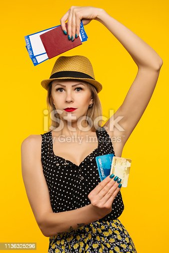 Young smiling excited woman student holding passport boarding pass ticket and credit card isolated on yellow background. Air travel flight - Image