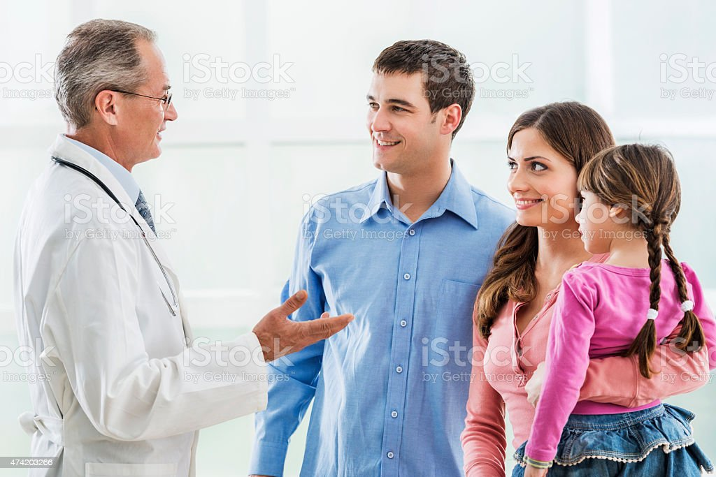 Young smiling family communicating with a mature doctor. stock photo