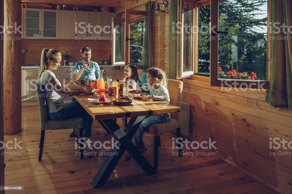 Young smiling family enjoying in breakfast at dining table. royalty-free stock photo