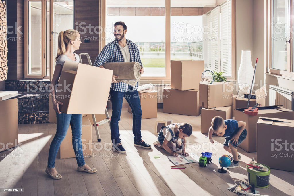 Young smiling family moving into a new apartment. stock photo