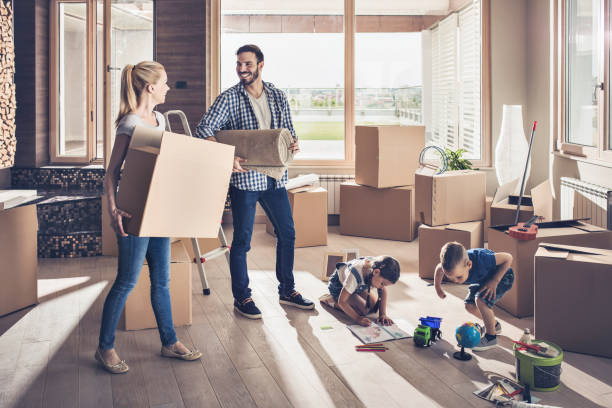 young smiling family moving into a new apartment. - happy mom packing some toys stock photos and pictures