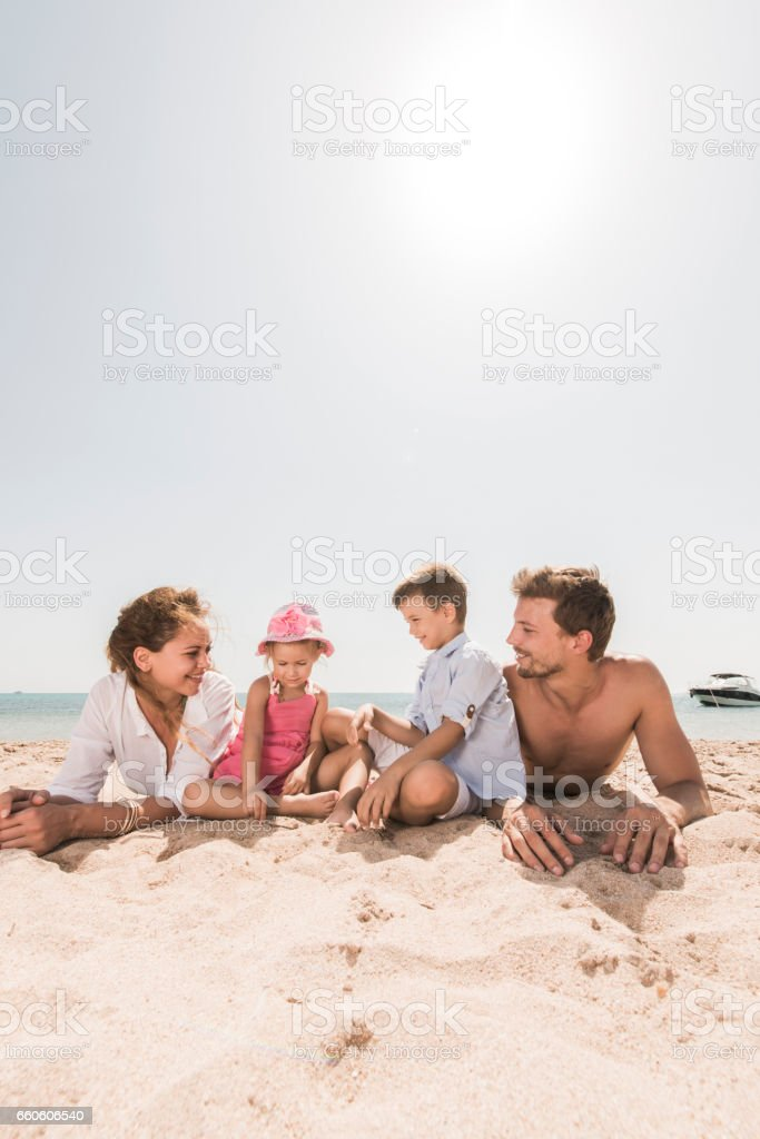 Young smiling family relaxing in sand on the beach. royalty-free stock photo