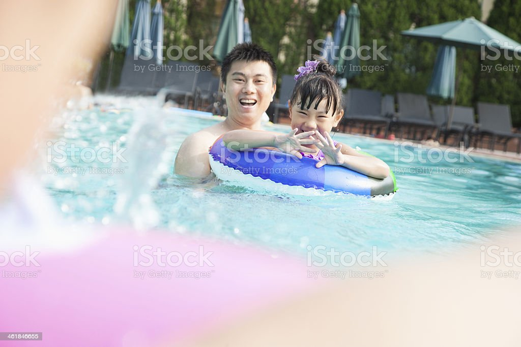 Young smiling family splashing and playing in the pool stock photo