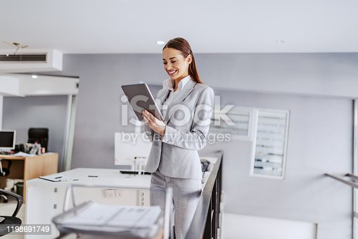 istock Young smiling female director in suit standing in office and using tablet. Corporate business concept. 1198691749