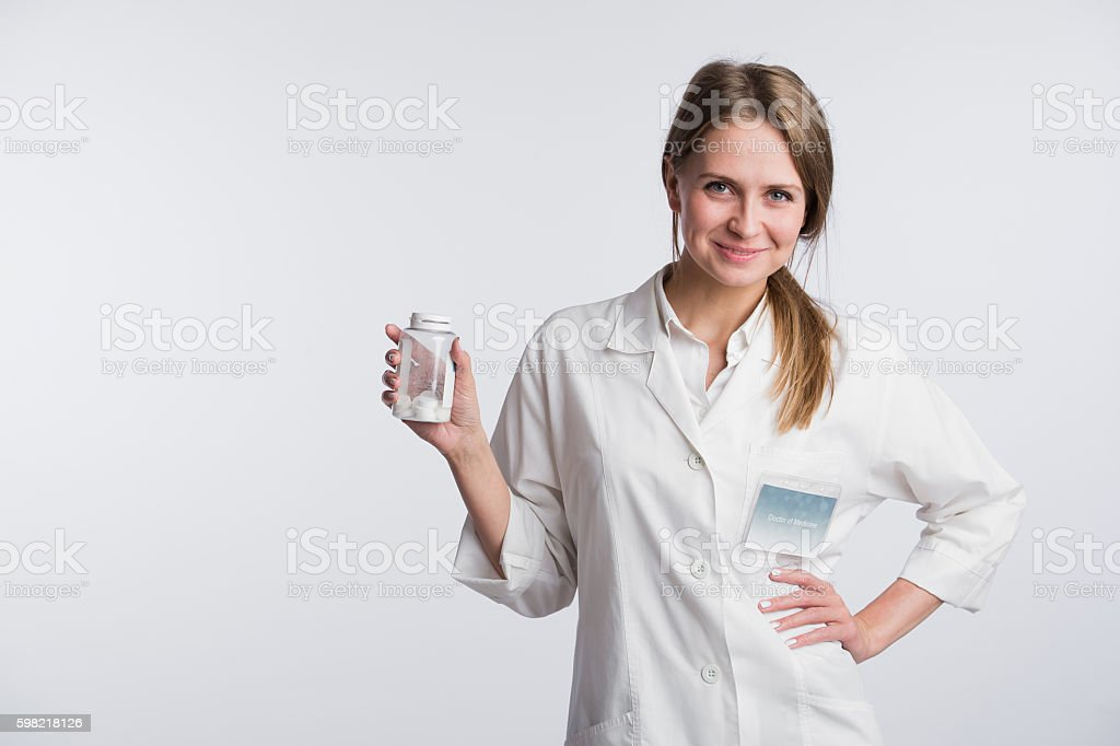 Young smiling female doctor presenting a white unlabeled bottle or foto royalty-free
