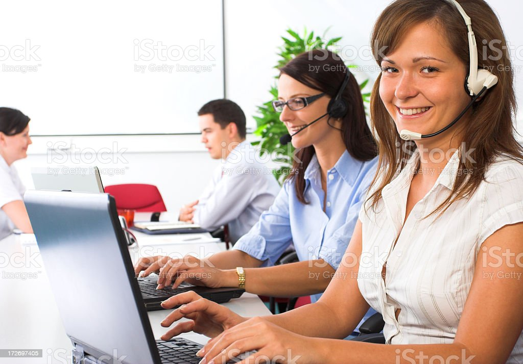 Young smiling female helpdesk operator in foreground stock photo