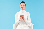 istock Young smiling female in eyeglasses, holding cup of coffee in hands, sitting in armchair, having rest from work, isolated on blue background 1226086732