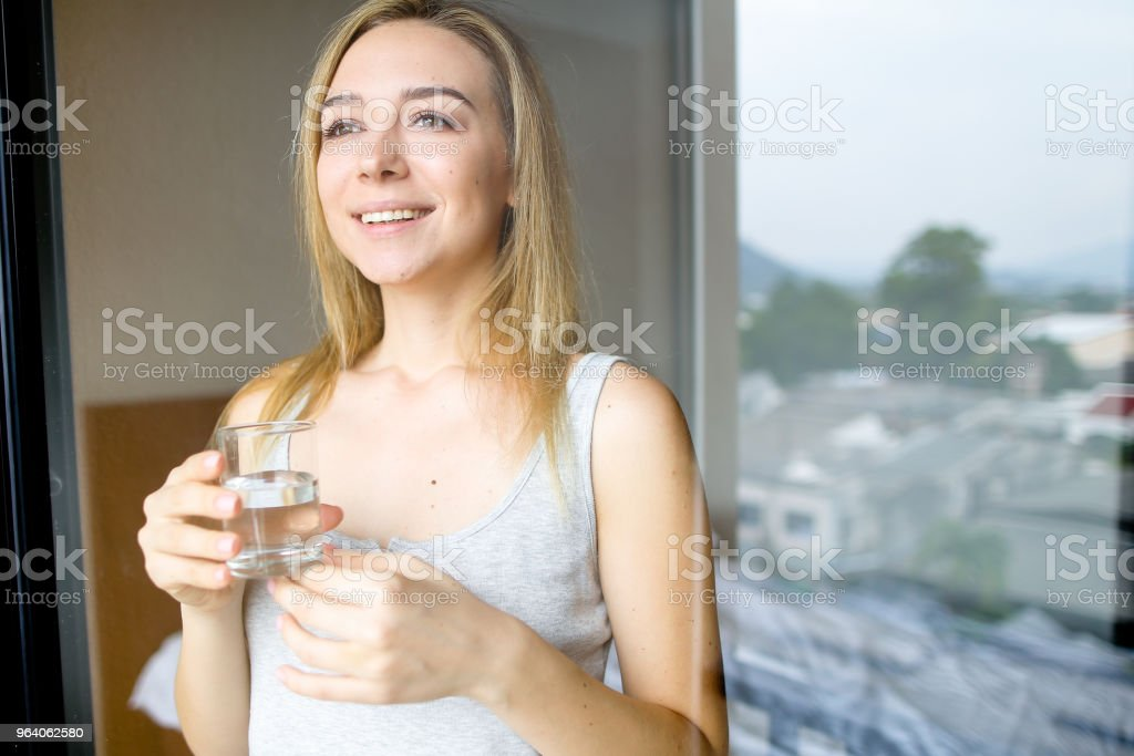 Young smiling female person drinking glass of water in morning at hotel - Royalty-free Adult Stock Photo