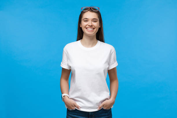 Young smiling female wearing white t-shirt, isolated on blue background Young smiling female wearing white t-shirt, isolated on blue background white t shirt stock pictures, royalty-free photos & images