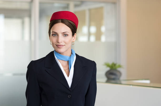 Young smiling flight assistant Portrait of young air hostess standing at airport and looking at camera. Portrait of flight assistant in uniform standing near check in counter. Happy agent wearing the hostess uniform at airport. cabin crew stock pictures, royalty-free photos & images