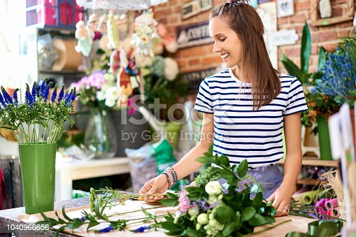 Young smiling florist holding bouquet of flowers and adding decorative elements