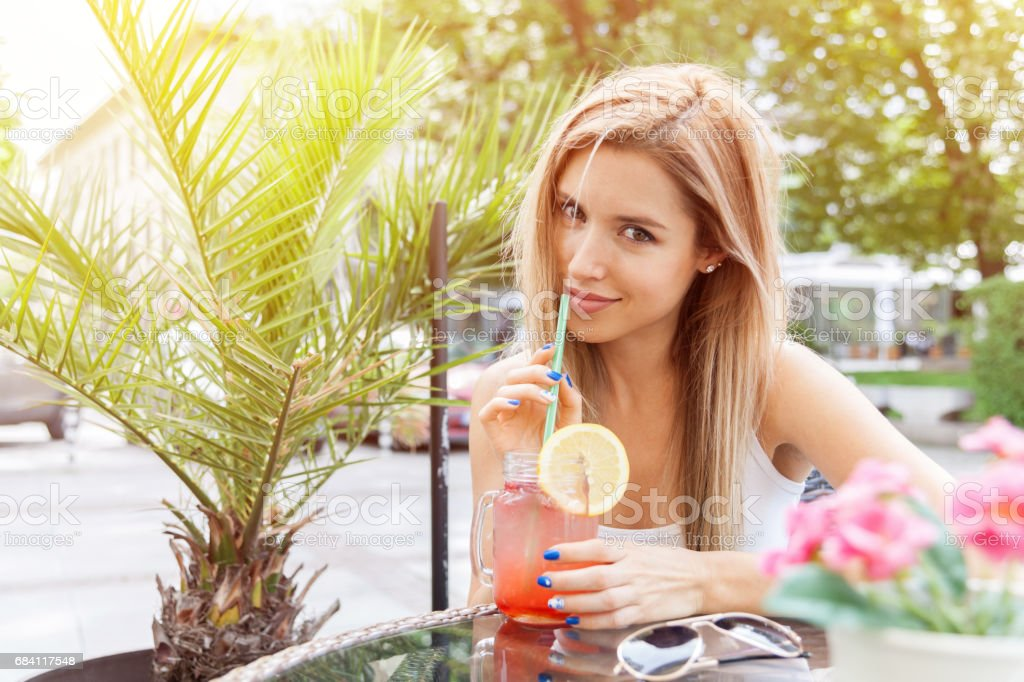 Young smiling girl drinking tasty cocktail , outdoor zbiór zdjęć royalty-free