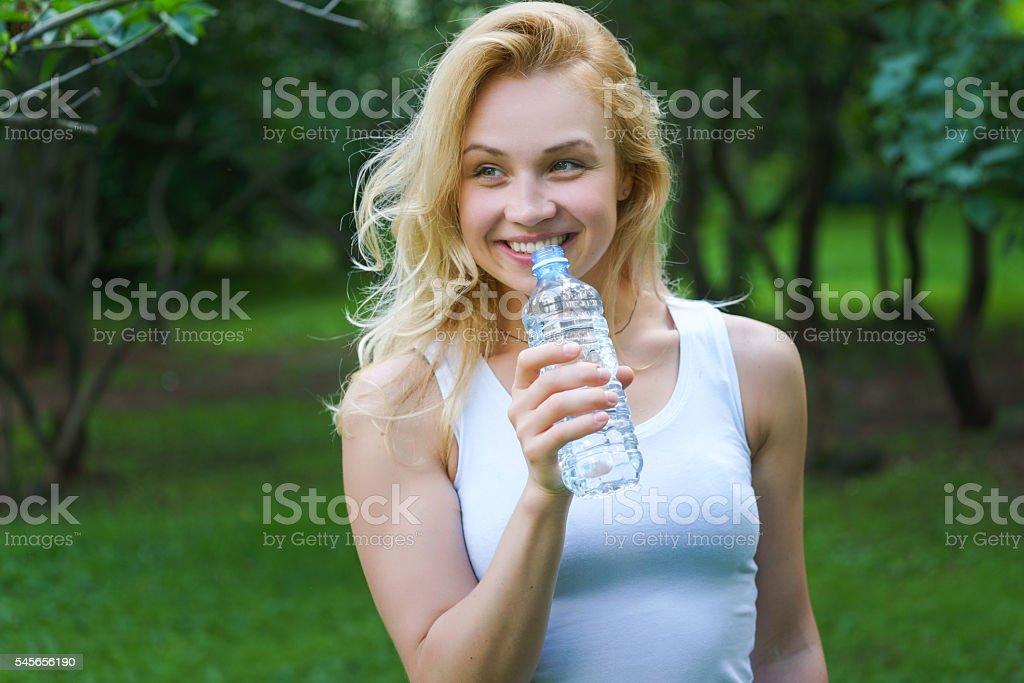 Young smiling girl drinking water from bottle stock photo