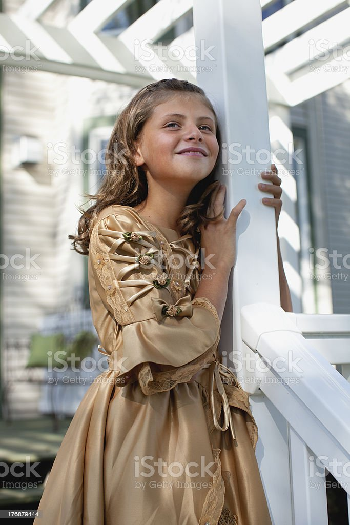 Young smiling girl in vintage style dress on white porch royalty-free stock photo