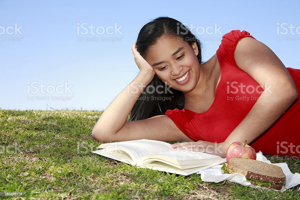 Young Smiling Girl Reading and Relaxing at the Park royalty-free stock photo