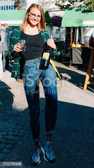 Young smiling girl wearing glasses holds wine bottle and glass. Woman casual style. Female person having fun. Happy holiday celebration. Outdoors lifestyle portrait. Adult beautiful face. Street event
